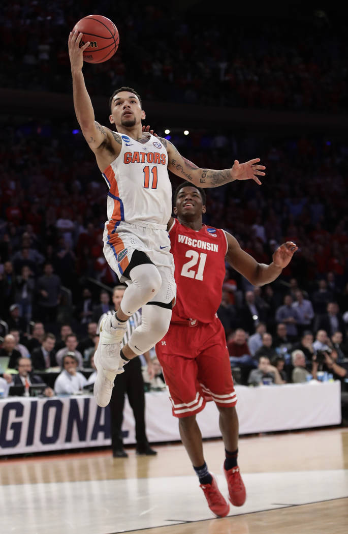 Florida guard Chris Chiozza (11) goes up for a shot against Wisconsin guard Khalil Iverson (21) in overtime of an East Regional semifinal game of the NCAA men's college basketball tournament, Satu ...