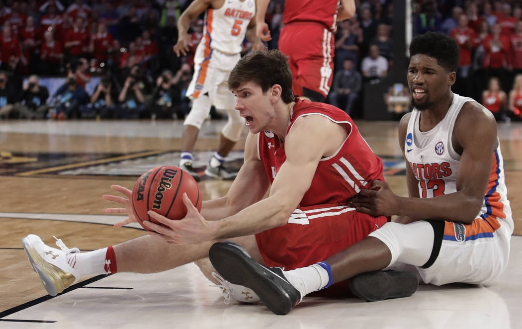 Wisconsin forward Ethan Happ (22) looks to get a pass off against Florida forward Kevarrius Hayes (13) in overtime of an East Regional semifinal game of the NCAA men's college basketball tournamen ...