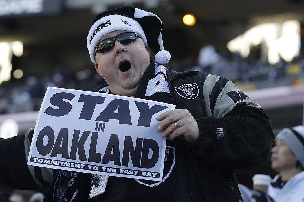 A fan hold up a sign about the Oakland Raiders' possible franchise move before an NFL football game between the Oakland Raiders and the Indianapolis Colts in Oakland, Calif., Saturday, Dec. 24, 20 ...
