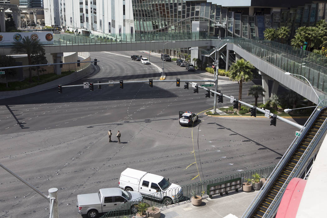 Pedestrian walkways, streets and sideways are empty while officers patrol at the intersection of Las Vegas Blvd. and Harmon Ave., just south the barricade, on Saturday, March 25, 2017, in Las Vega ...
