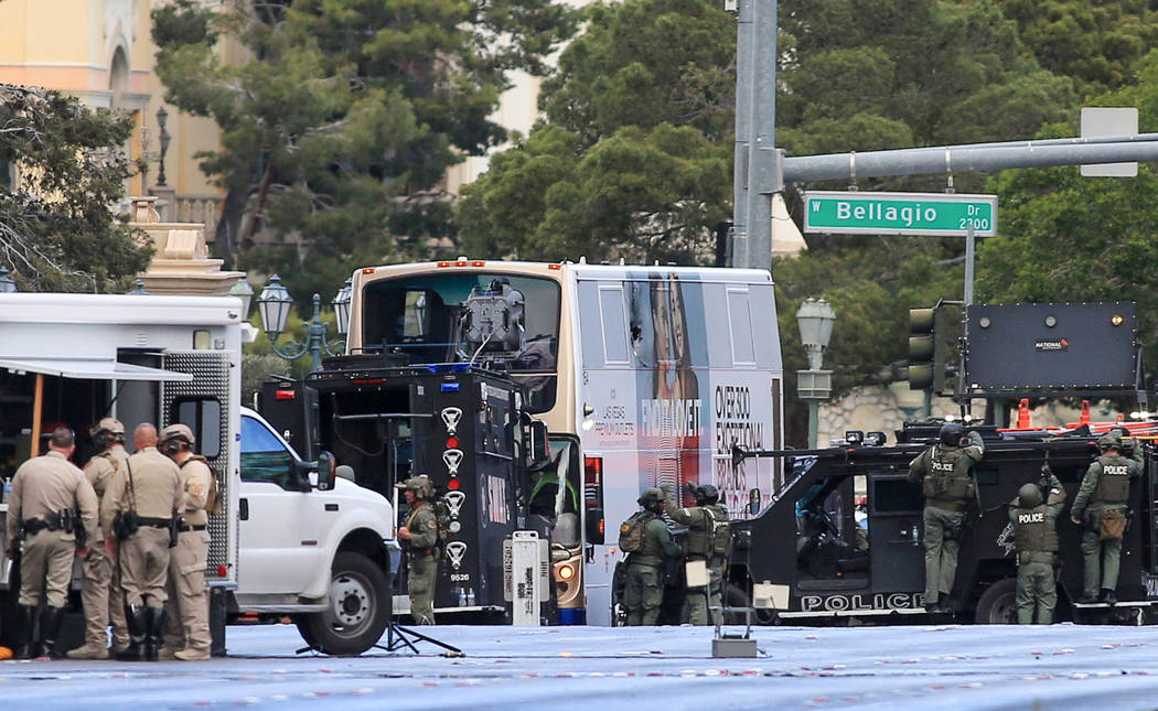 Las Vegas police work the scene of a barricaded suspect in a bus outside the outside of the Cosmopolitan hotel-casino in Las Vegas on Saturday, March 25, 2017. The suspect surrendered to police af ...