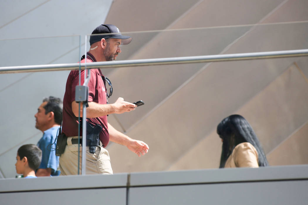 An armed security guard walks along a pedestrian bridge near the scene of a barricaded suspect in a bus on Las Vegas Boulevard in Las Vegas on Saturday, March 25, 2017. (Brett Le Blanc/Las Vegas R ...