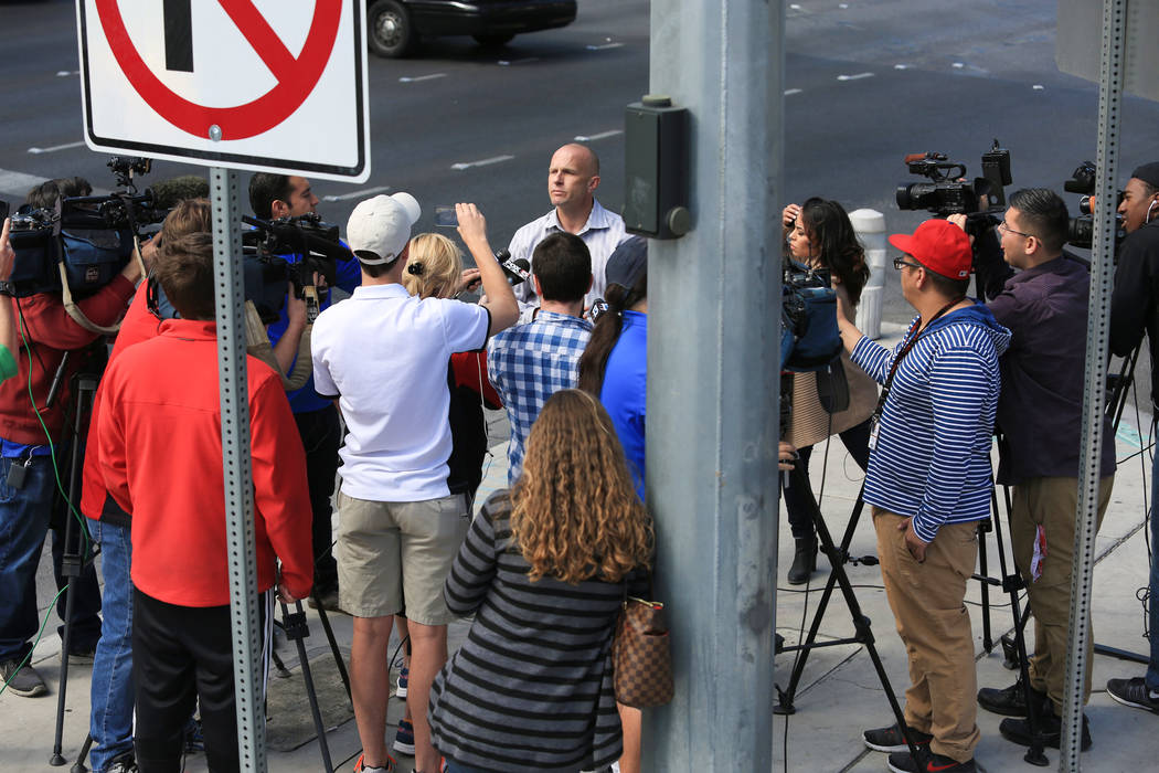 Las Vegas Metropolitan police department spokesman Ofc. Larry Hadfield briefs the media on the barricade situation taking place on a bus outside of the Cosmopolitan hotel-casino in Las Vegas on Sa ...