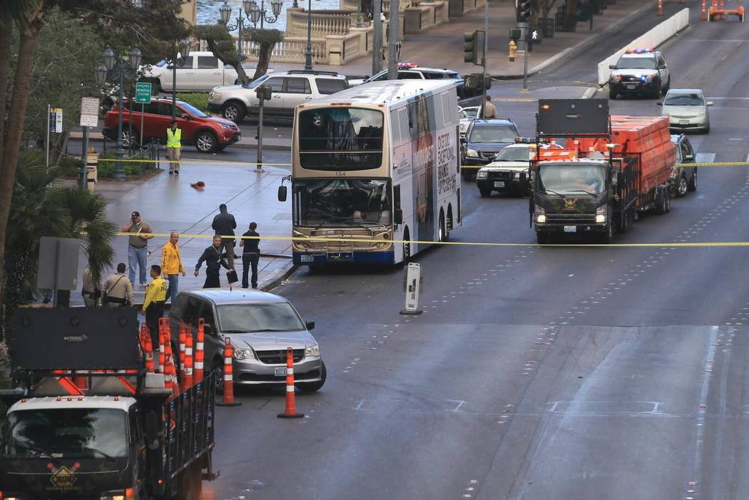Police investigate the scene of a shooting on an RTC bus that left one person dead and one injured outside the Cosmopolitan on Saturday, March 25, 2017. The suspect in the shooting surrendered to  ...