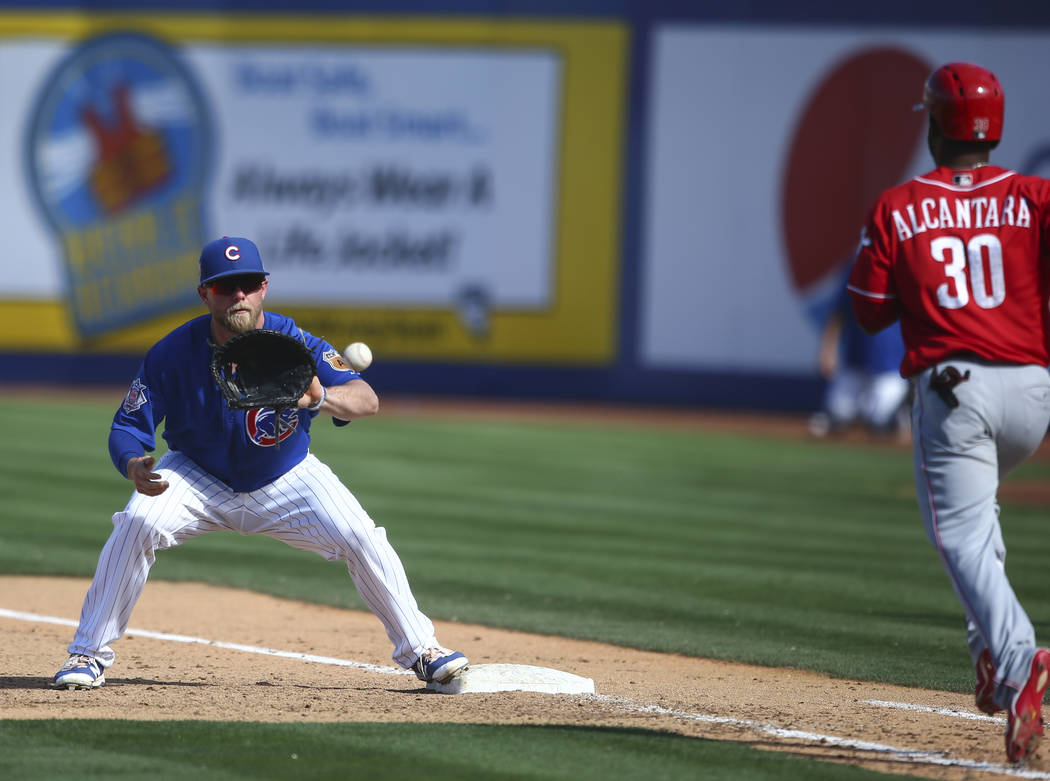 Chicago Cubs' Taylor Davis (82) gets Cincinnati Reds' Arismendy Alcantara (30) out at first base during their Big League Weekend baseball game at Cashman Field in Las Vegas on Saturday, March 25,  ...