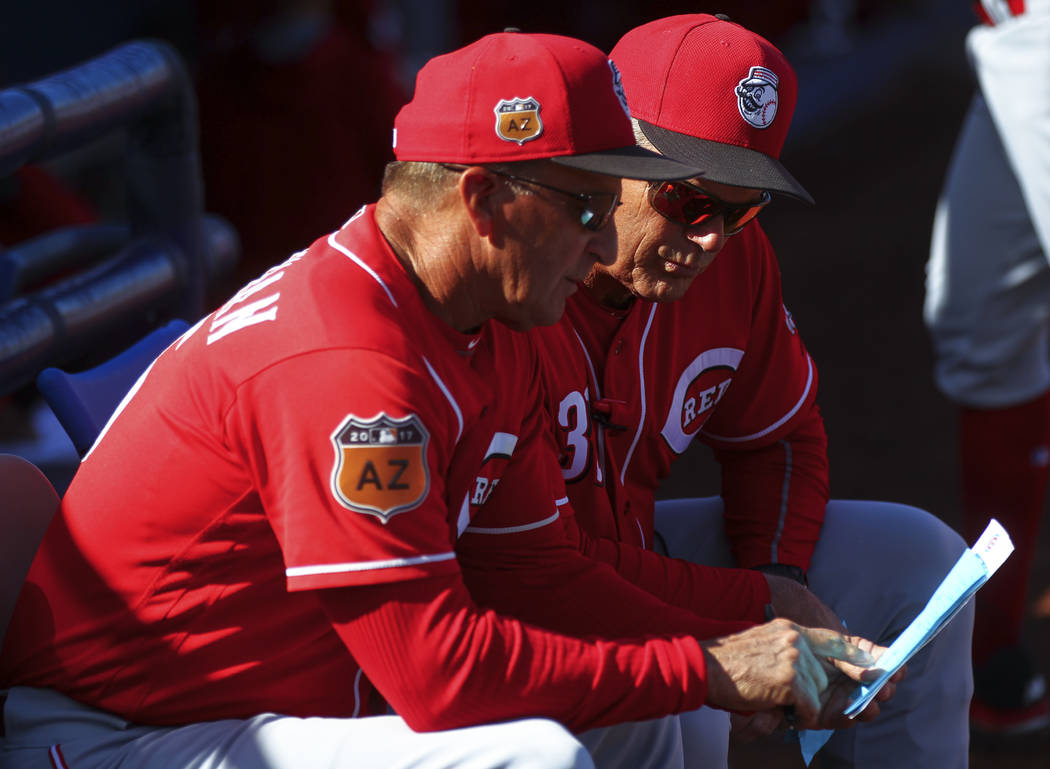 Cincinnati Reds manager Jim Riggleman, left, and first base coach Pat Kelly talk during their Big League Weekend baseball game against the Chicago Cubs at Cashman Field in Las Vegas on Saturday, M ...