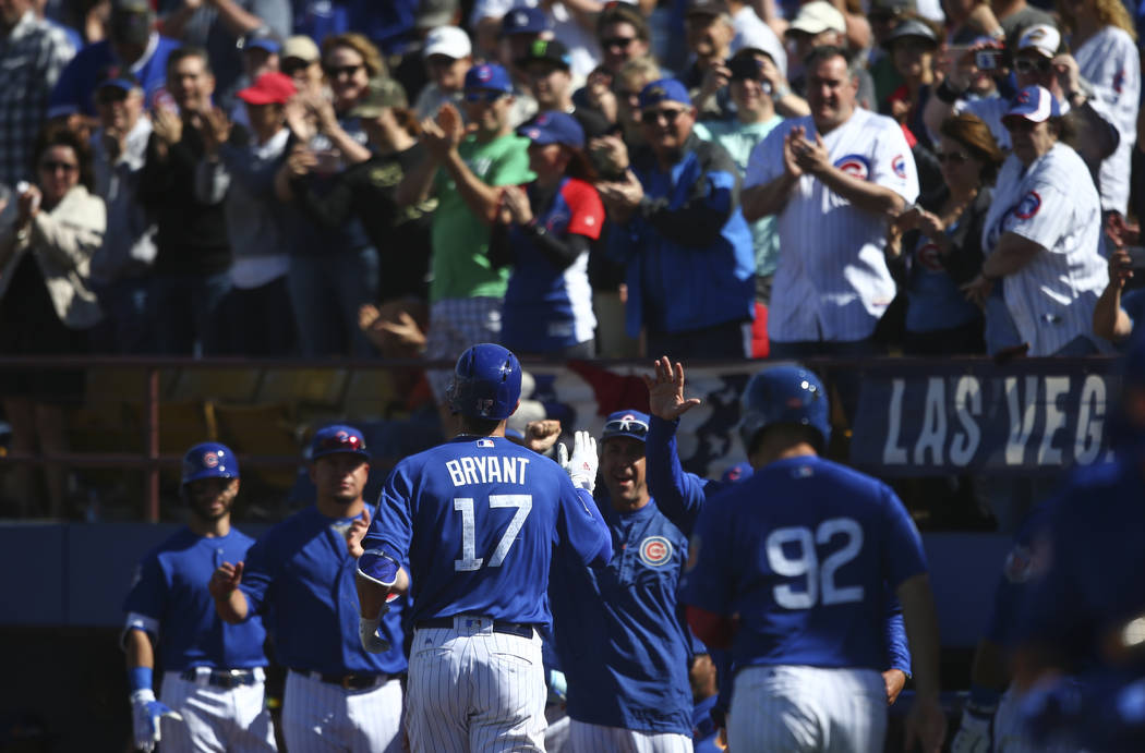 Chicago Cubs' Kris Bryant (17) returns to the dugout after scoring a home run against the Cincinnati Reds during their Big League Weekend baseball game at Cashman Field in Las Vegas on Saturday, M ...