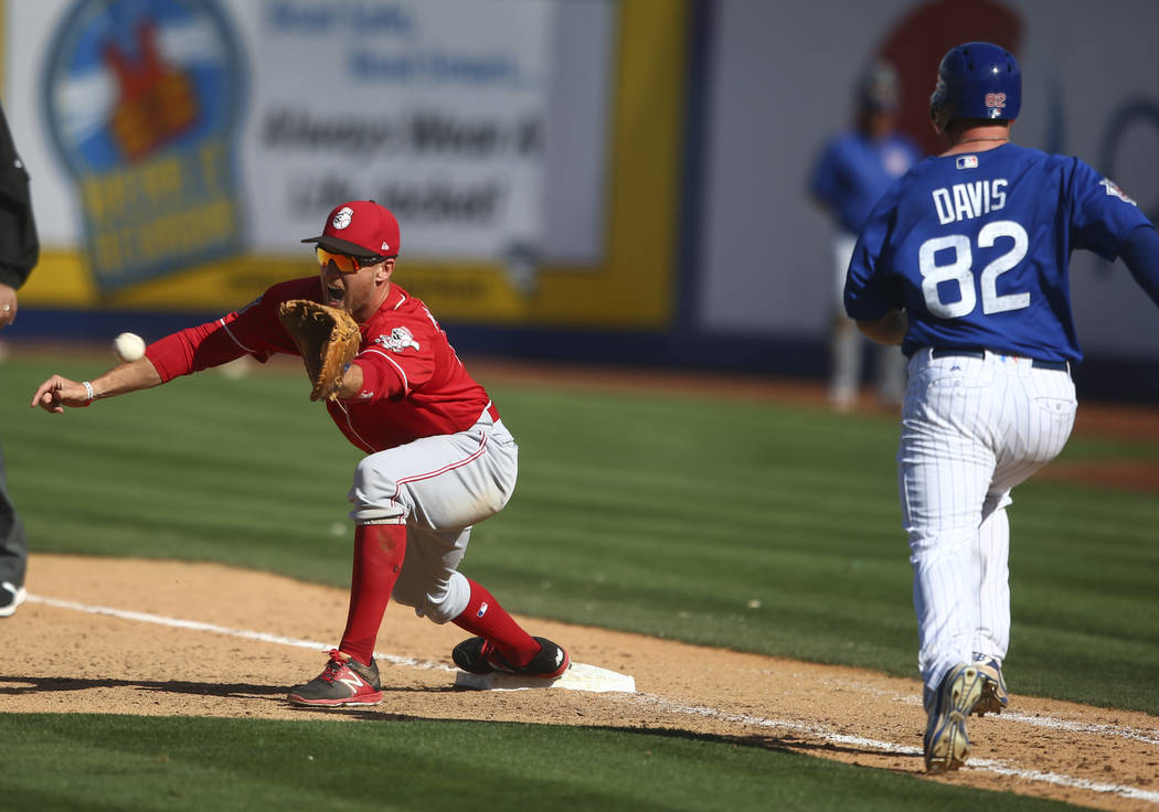Cincinnati Reds' Patrick Kivlehan (75) gets Chicago Cubs' Taylor Davis (82) out at first base during their Big League Weekend baseball game at Cashman Field in Las Vegas on Saturday, March 25, 201 ...