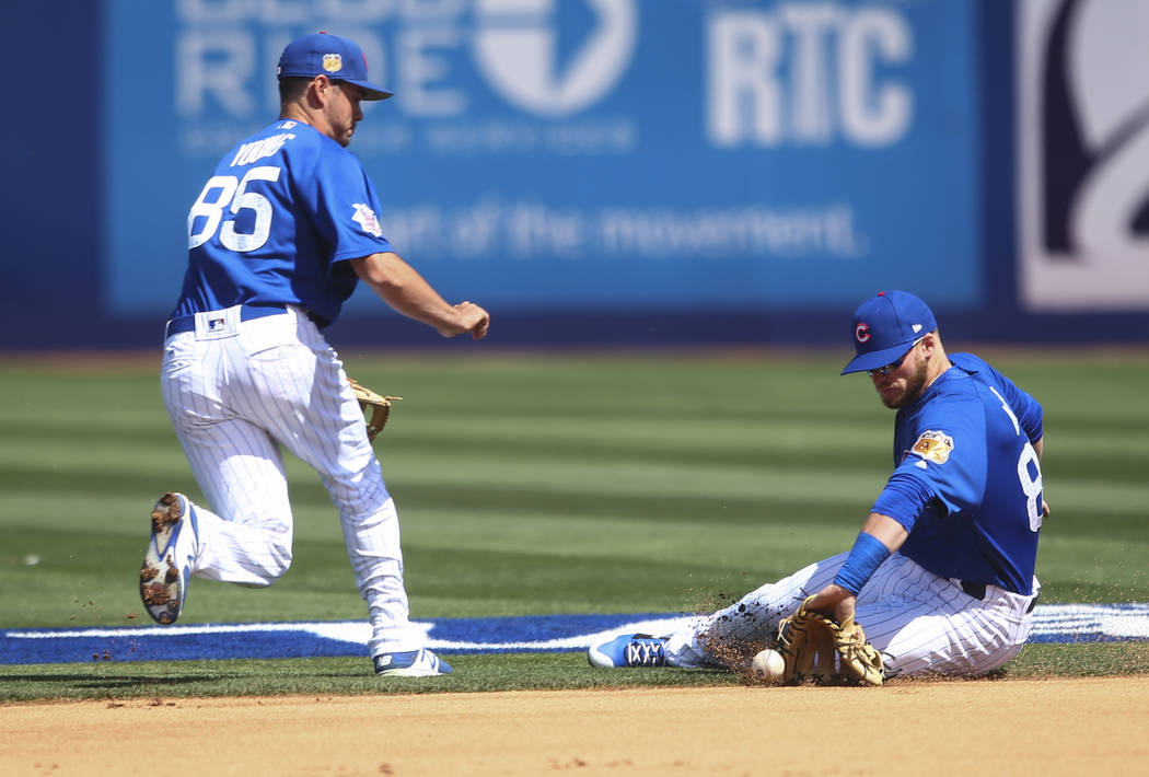 Chicago Cubs' Ian Happ (86) misses a grounder from Cincinnati Reds' Eugenio Suarez (7) as Chicago Cubs' Chesny Young (85) looks on during their Big League Weekend baseball game at Cashman Field in ...