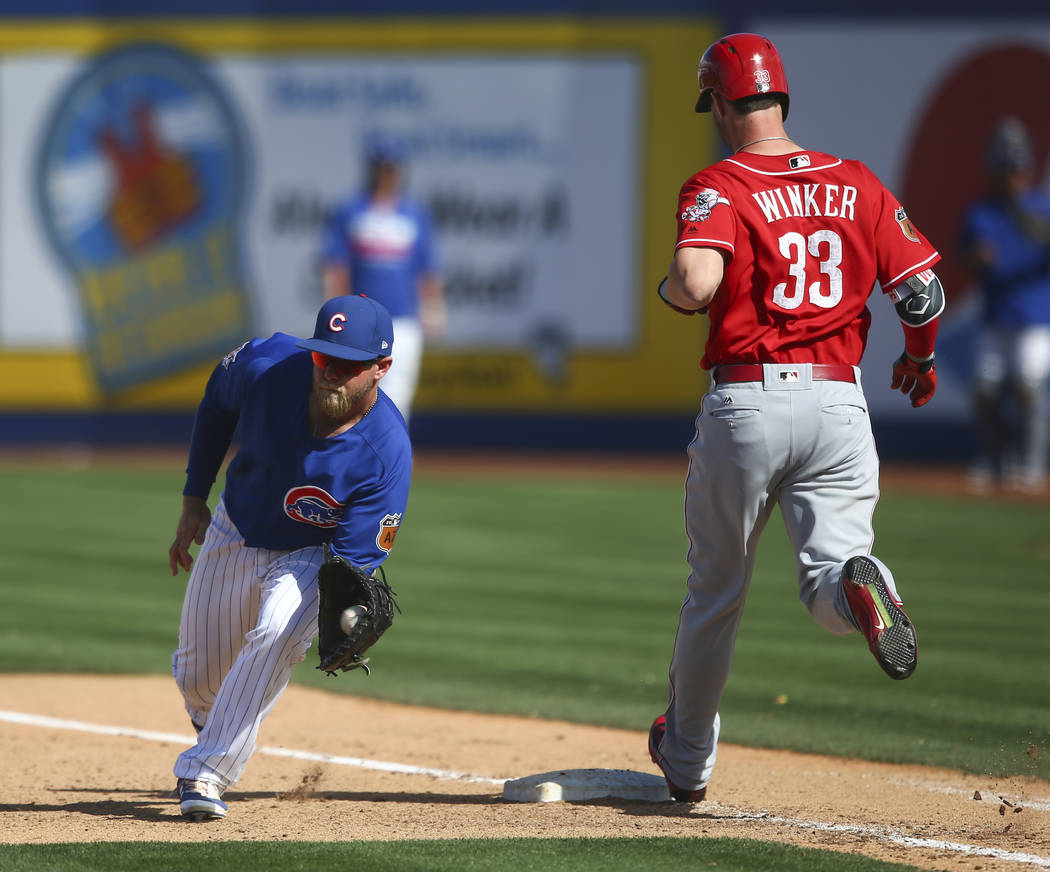 Cincinnati Reds' Jesse Winker (33) gets to first base against Chicago Cubs' Taylor Davis (82) during their Big League Weekend baseball game at Cashman Field in Las Vegas on Saturday, March 25, 201 ...