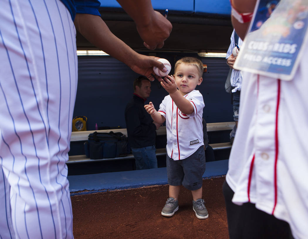 A young fan gets his ball signed by Chicago Cubs pitcher Daniel Corcino (55) before their Big League Weekend baseball game against the Cincinnati Reds at Cashman Field in Las Vegas on Saturday, Ma ...