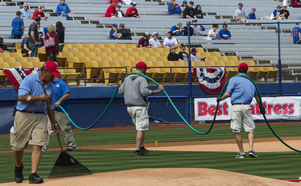 A crew prepares the diamond before the Cincinnati Reds play the Chicago Cubs for a Big League Weekend baseball game at Cashman Field in Las Vegas on Saturday, March 25, 2017. (Miranda Alam/Las Veg ...