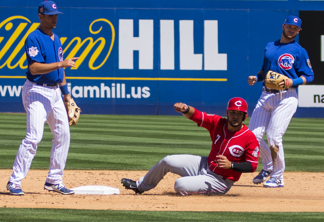 Cincinnati Reds third baseman Eugenio Suarez (7) slides into second base during their Big League Weekend baseball game against the Chicago Cubs at Cashman Field in Las Vegas on Saturday, March 25, ...
