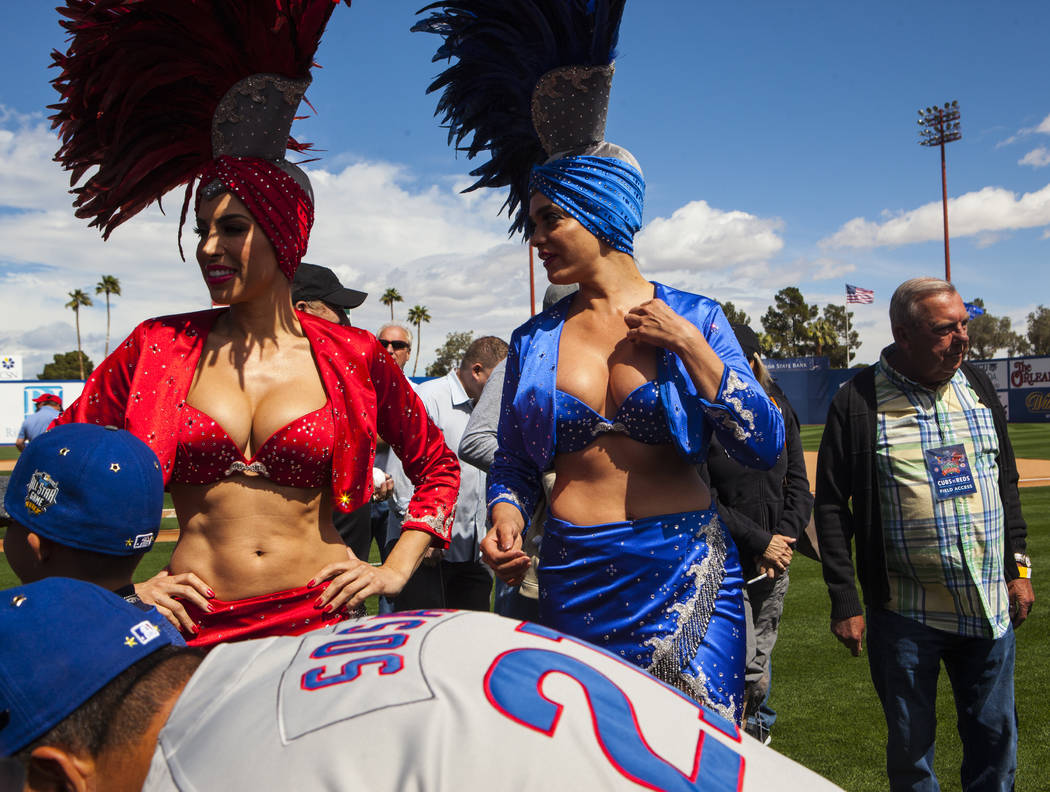 Las Vegas showgirls wait on the field to pose with fans before the Cincinnati Reds play the Chicago Cubs at the Big League Weekend baseball game at Cashman Field in Las Vegas on Saturday, March 25 ...