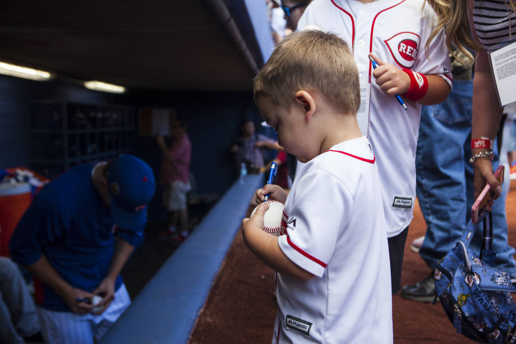 A young fan signs his own ball while waiting to have it signed by Chicago Cubs players before their Big League Weekend baseball game against the Cincinnati Reds at Cashman Field in Las Vegas on Sa ...