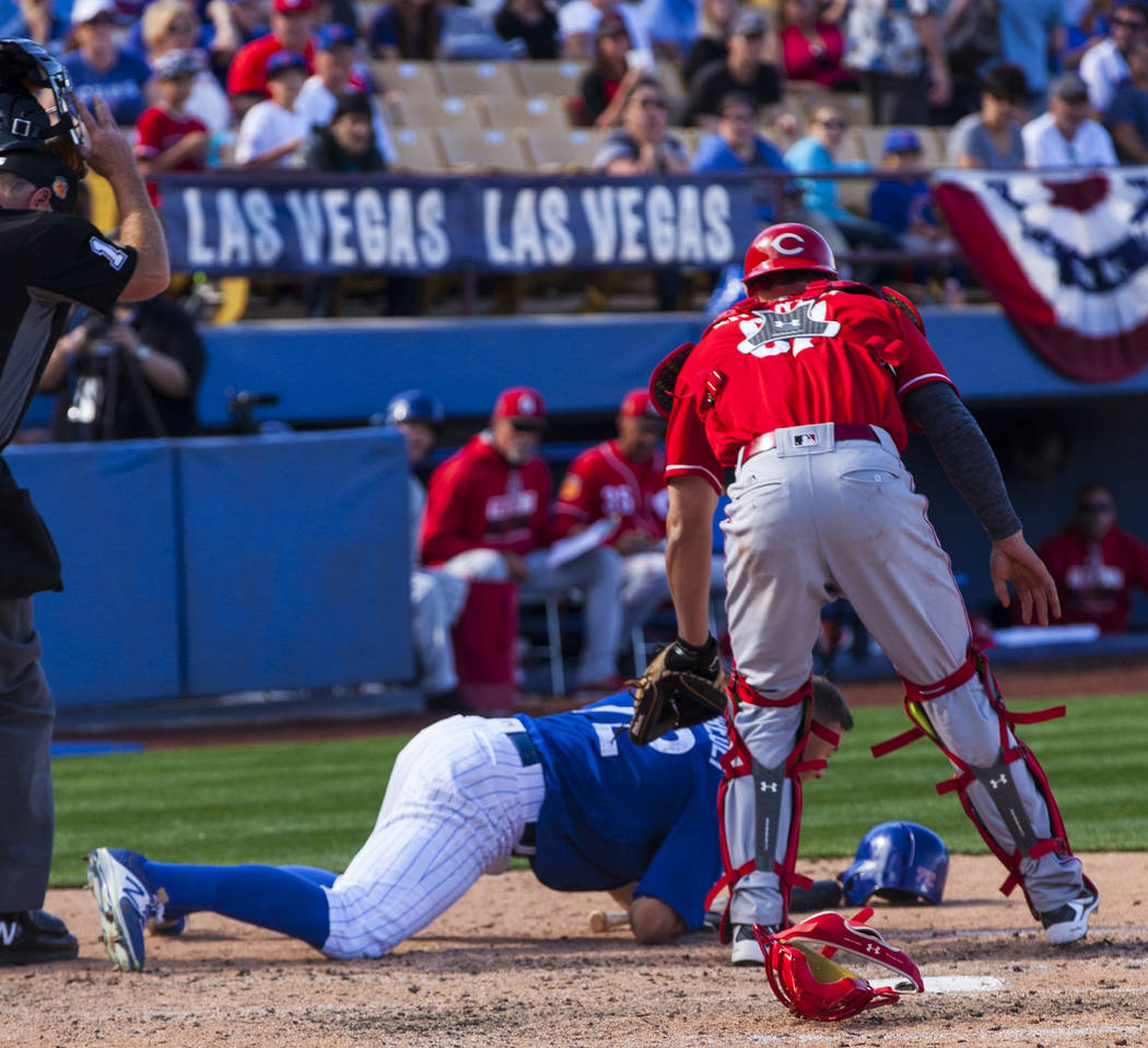 Chicago Cubs batter John Andreoli (72) falls to the ground after getting hit with the ball during their Big League Weekend baseball game at Cashman Field against the Cincinnati Reds in Las Vegas o ...