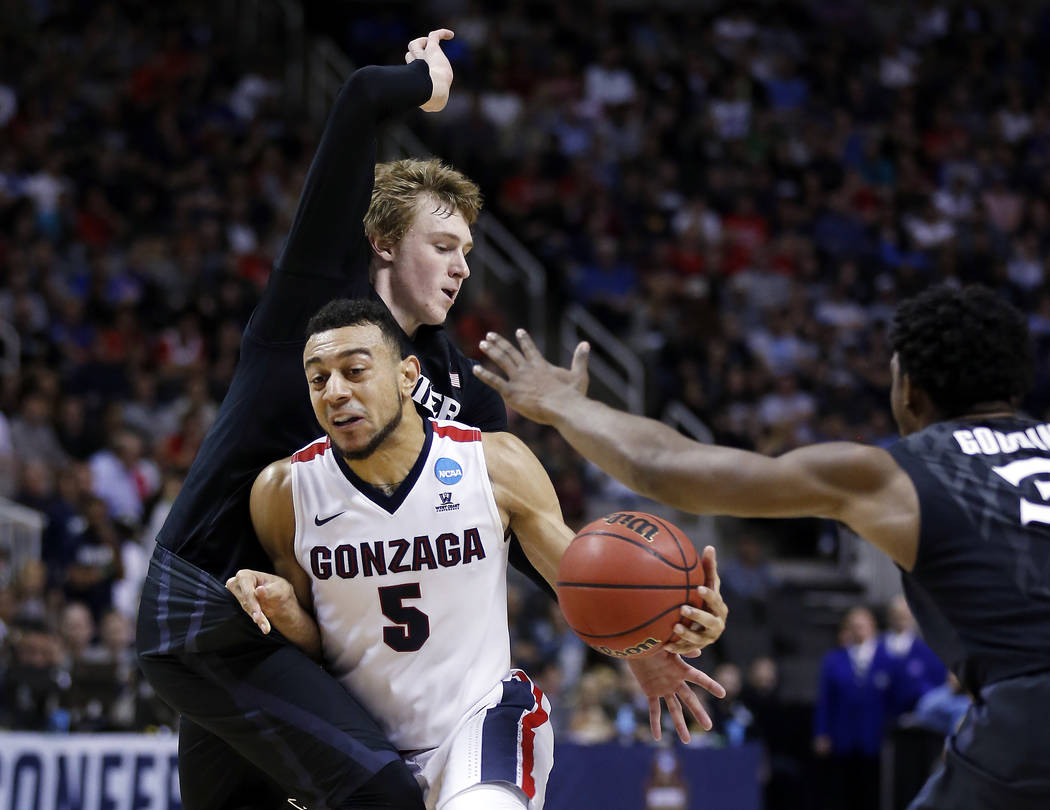 Gonzaga guard Nigel Williams-Goss (5) dribbles between Xavier guard J.P. Macura, left, and Quentin Goodin during the first half of an NCAA Tournament college basketball regional final game Saturda ...