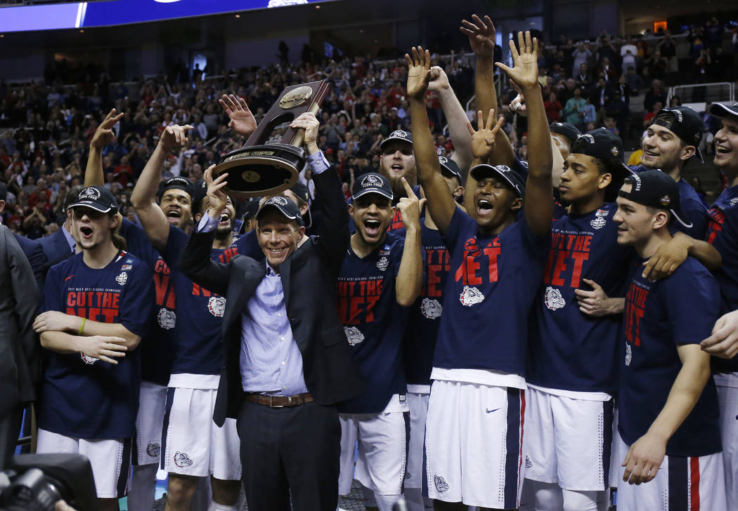 Gonzaga head coach Mark Few, center, holds a trophy with his team after beating Xavier during an NCAA Tournament college basketball regional final game Saturday, March 25, 2017, in San Jose, Calif ...