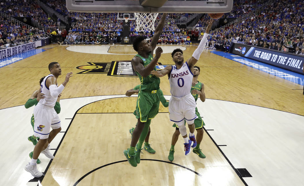 Kansas guard Frank Mason III (0) drives to the basket past Oregon forward Jordan Bell during the first half of a regional final of the NCAA men's college basketball tournament, Saturday, March 25, ...