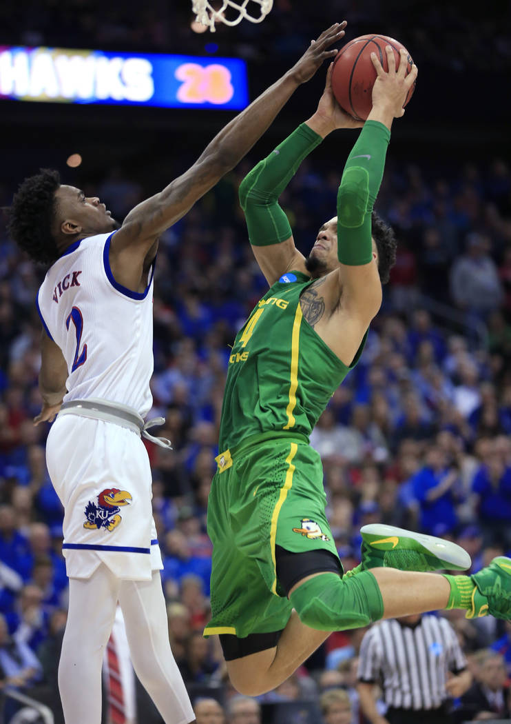 Oregon forward Dillon Brooks, right, shoots over Kansas guard Lagerald Vick during the first half of the Midwest Regional final of the NCAA men's college basketball tournament, Saturday, March 25, ...