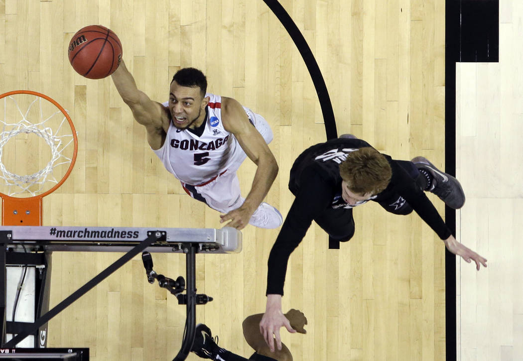 Gonzaga guard Nigel Williams-Goss (5) shoots past Xavier guard J.P. Macura during the second half of an NCAA Tournament college basketball regional final game Saturday, March 25, 2017, in San Jose ...