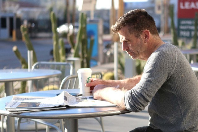 Steve Stenberg takes advantage of the sunny weather to read his paper outside a Starbucks in downtown Las Vegas on Friday, Feb 3, 2017. (Bizuayehu Tesfaye/Las Vegas Review-Journal) @bizutesfaye