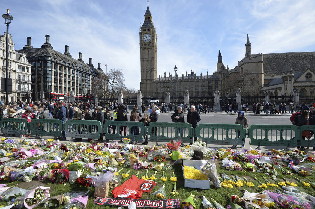 People look at tributes in Parliament Square, London, Saturday March 25, 2017, laid out for the victims of the Westminster attack on Wednesday. Khalid Masood killed four people and left more than  ...