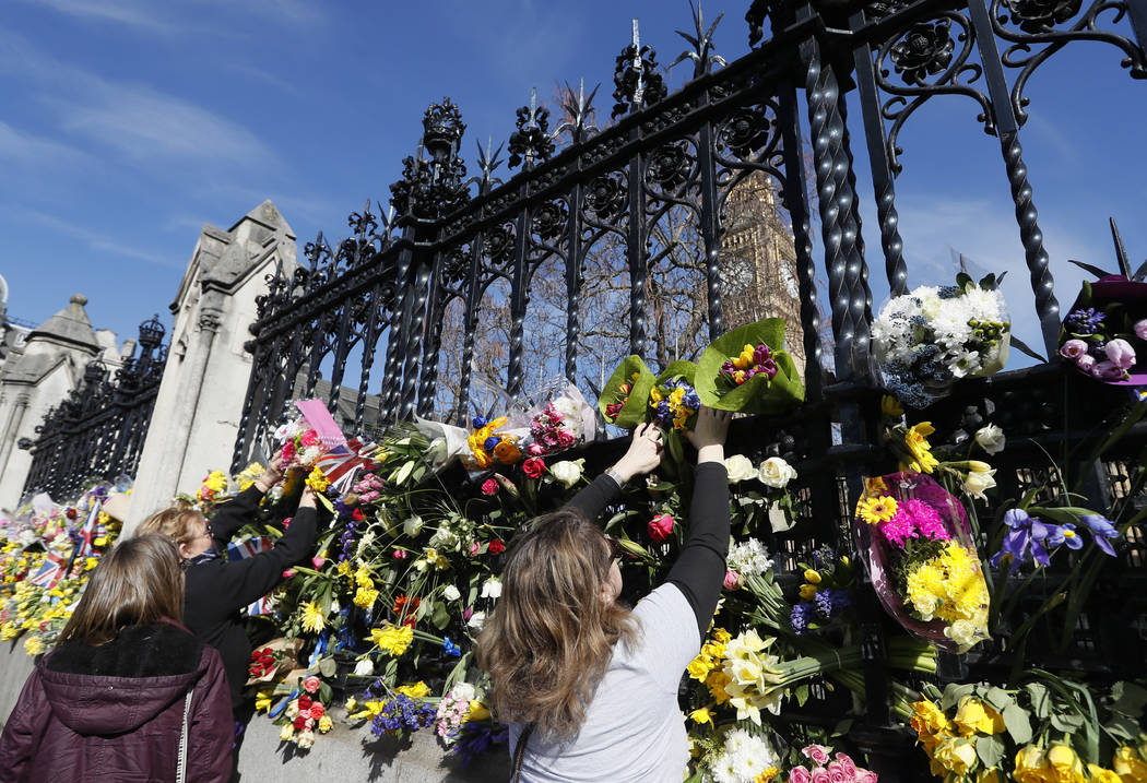 People place flowers outside Britain's parliament in London, Saturday March 25, 2017, for the victims of the Westminster attack on Wednesday. Khalid Masood killed four people and left more than tw ...