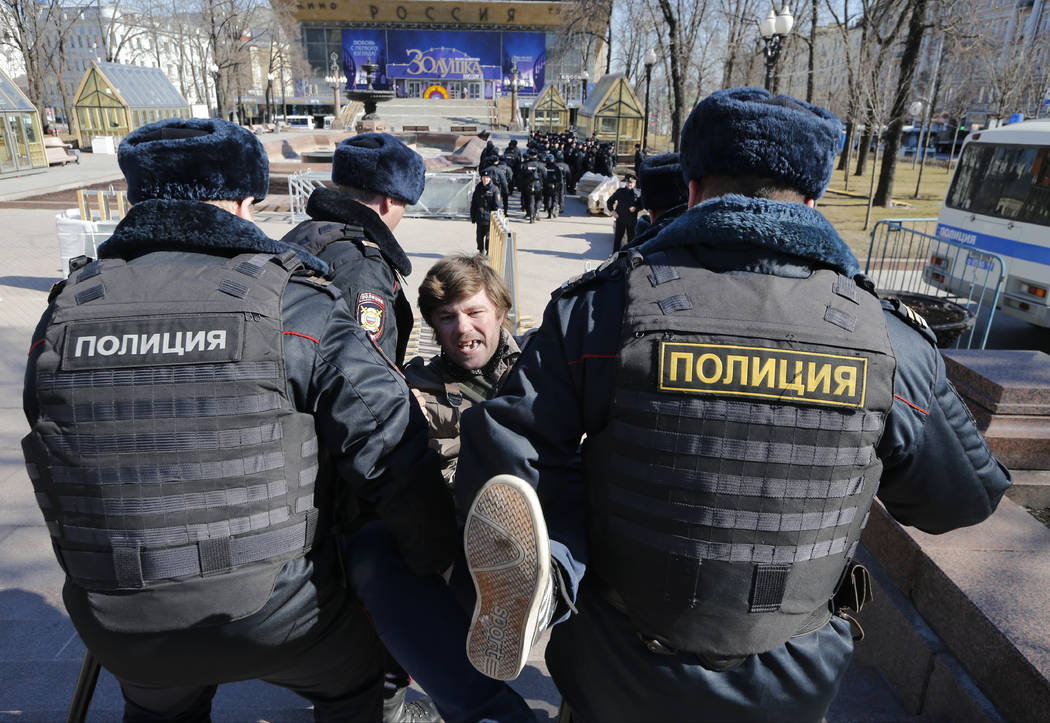 Police detain a protester in downtown Moscow, Russia, Sunday, May 26, 2017. Russia's leading opposition figure Alexei Navalny and his supporters aim to hold anti-corruption demonstrations througho ...