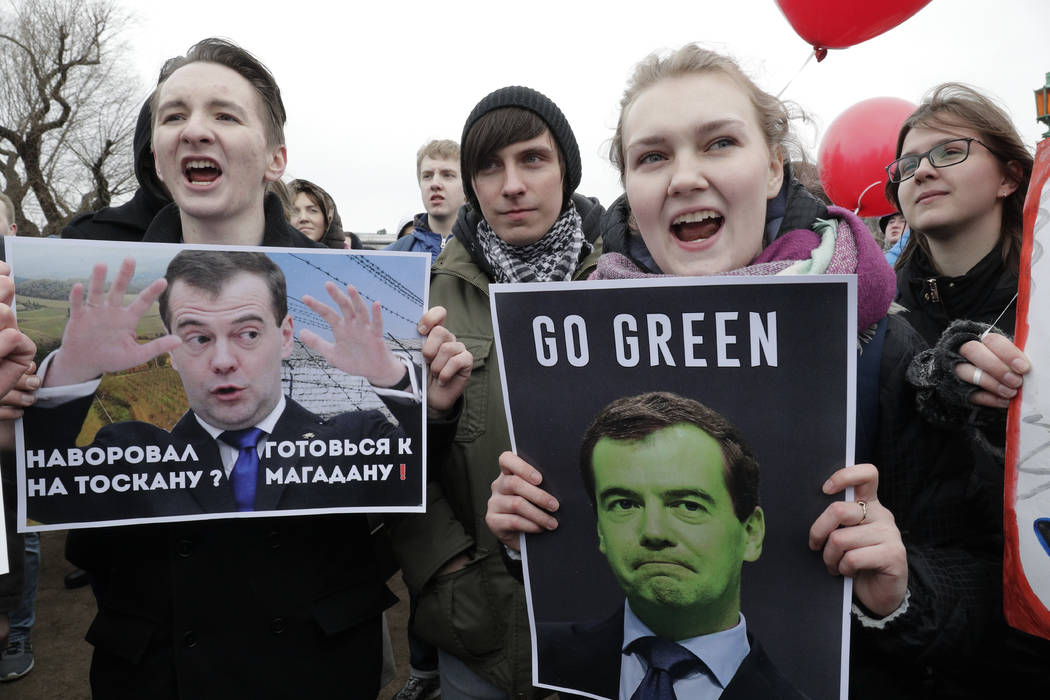 Protesters hold posters depicting Russian Prime Minister Dmitry Medvedev at Marsivo Field in St.Petersburg, Russia, Sunday, March 26, 2017. Thousands of people crowded in St.Petersburg on Sunday f ...