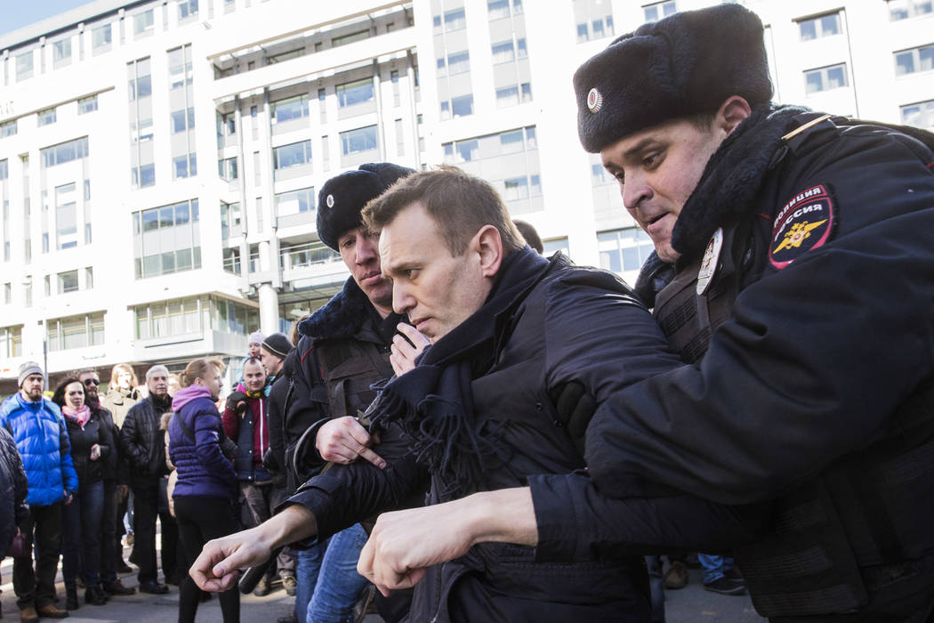In this photo provided by Evgeny Feldman, Alexei Navalny is detained by police in downtown Moscow, Russia, Sunday, March 26, 2017. Russia's leading opposition figure Alexei Navalny and his support ...