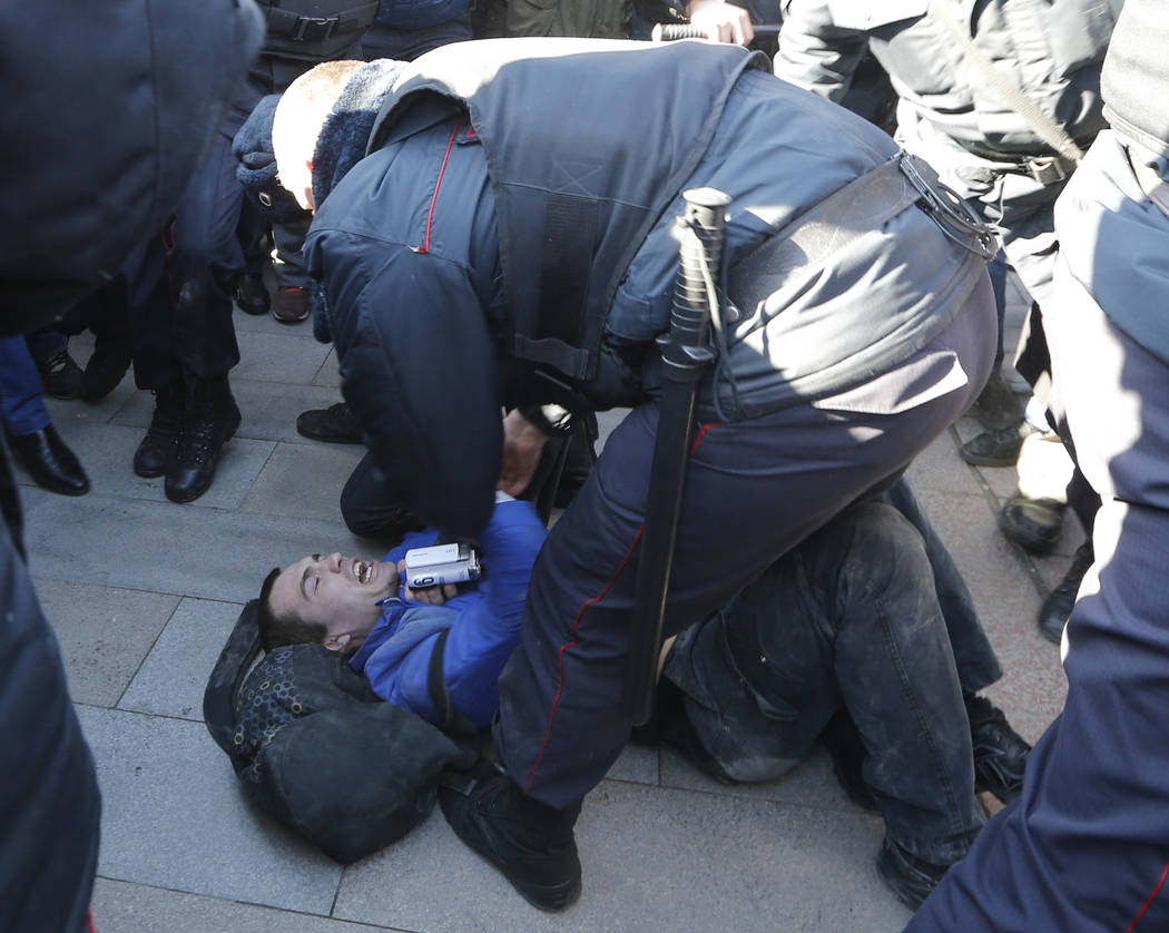 Police detain a protester in downtown Moscow, Russia, Sunday, March 26, 2017. Russia's leading opposition figure Alexei Navalny and his supporters aim to hold anti-corruption demonstrations throug ...