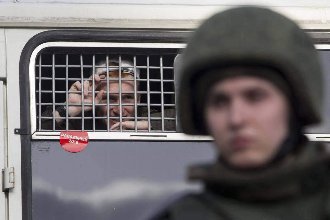 """A detained protester looks out of a police bus window with a red sticker reading """"Navalny"""" in downtown Moscow, Russia, Sunday, March 26, 2017. Russia's leading opposition figure Alexei Navalny and ..."""