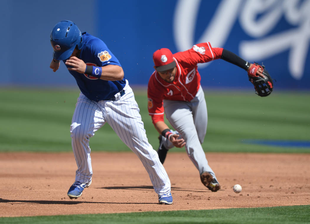 Chicago Cubs runner John Andreoli (73) takes off for third base while Cincinnati Reds short stop Eugenio Suarez (7) barehands a ground ball during a game between the Chicago Cubs and the Cincinnat ...