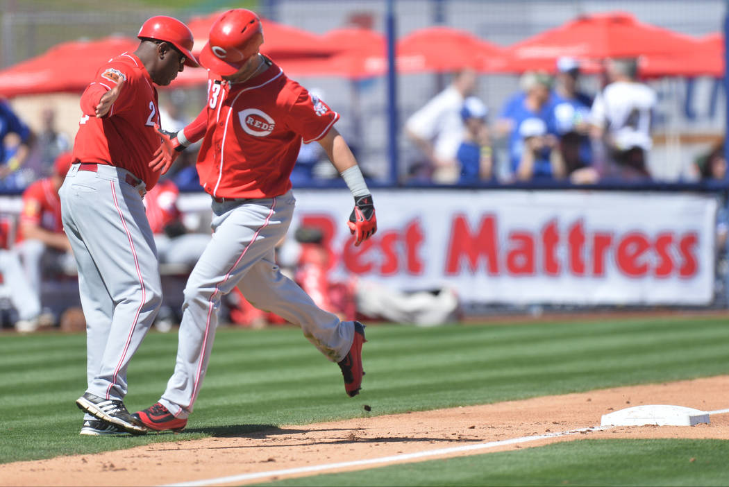 Cincinnati Reds Jesse Winker (33) high fives the third base coach Billy Hatcher after hitting a home run during a game between the Chicago Cubs and the Cincinnati Reds at Cashman Field in Las Vega ...