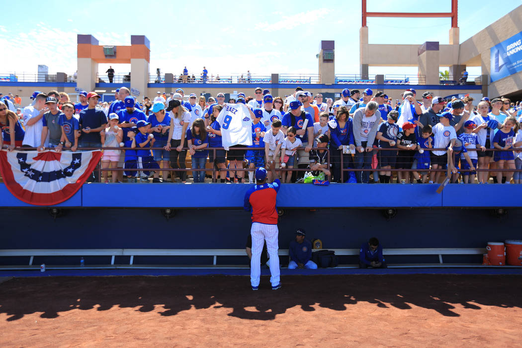 Fans bring everything from baseballs to license plates to get autographs from players before a game between the Chicago Cubs and the Cincinnati Reds at Cashman Field in Las Vegas on Sunday, March  ...