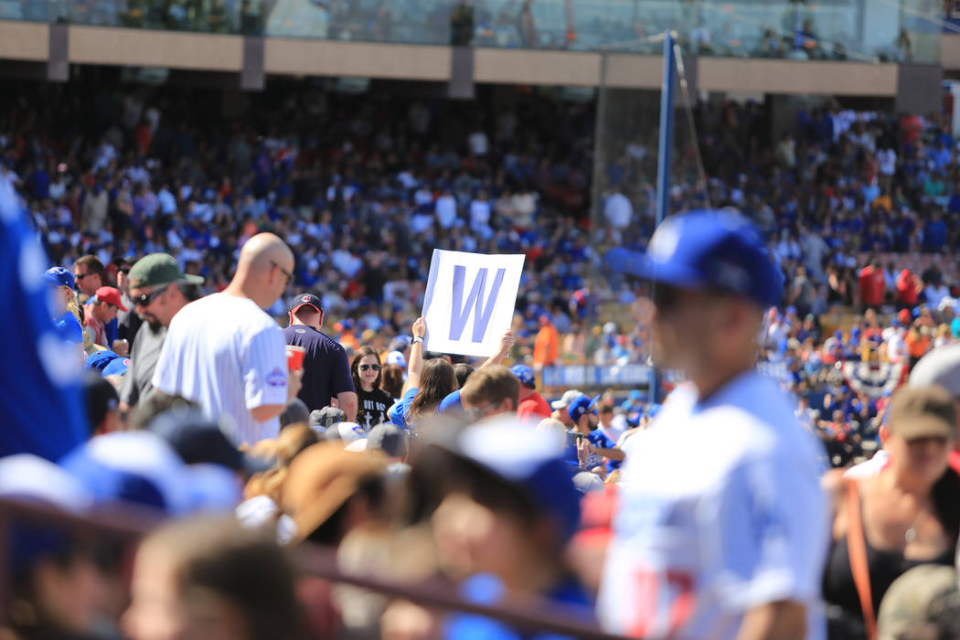 "A fan lifts a ""W"" sign to cheer for the Cubs during a game between the Chicago Cubs and the Cincinnati Reds at Cashman Field in Las Vegas on Sunday, March 26, 2017. (Brett Le Bla ..."