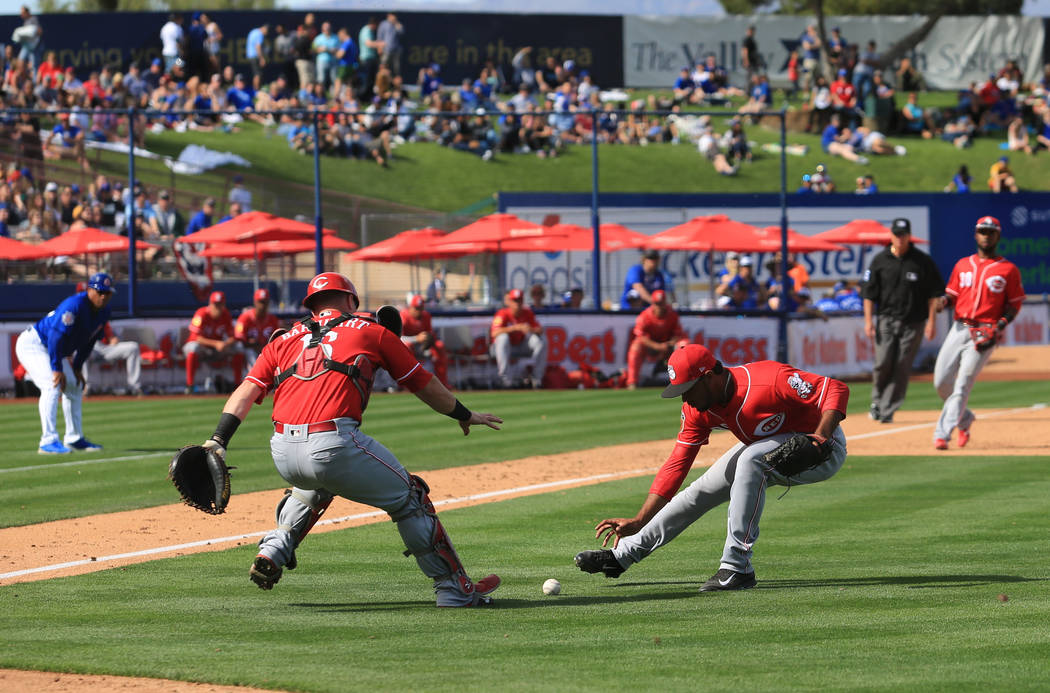 Cincinnati Reds pitcher Sandy Lugo (90) and catcher Tucker Barnhart (16) field a ball during a game between the Chicago Cubs and the Cincinnati Reds at Cashman Field in Las Vegas on Sunday, March  ...