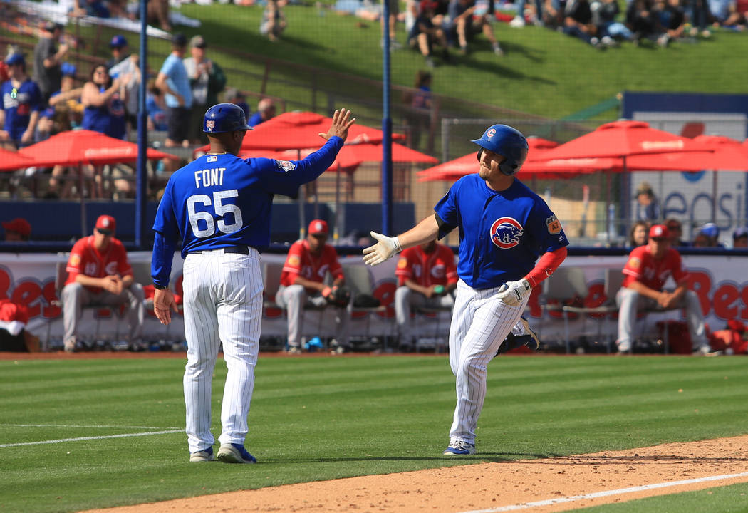 Chicago Cubs outfielder Bijan Rademacher (92) high fives the third base coach after hitting a grand slam during a game between the Chicago Cubs and the Cincinnati Reds at Cashman Field in Las Vega ...