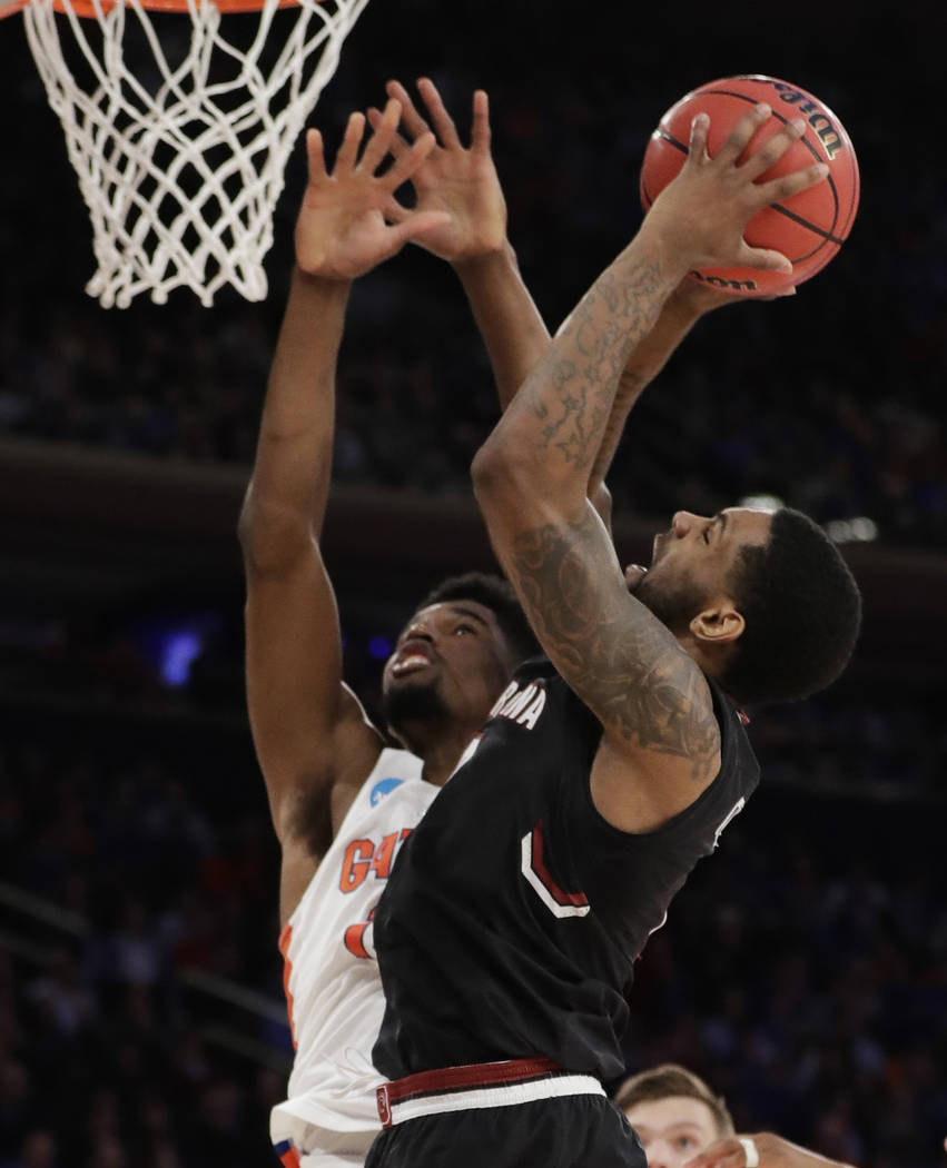 South Carolina guard Sindarius Thornwell (0) puts up a shot against Florida forward Kevarrius Hayes (13) during the second half of the East Regional championship game of the NCAA men's college bas ...
