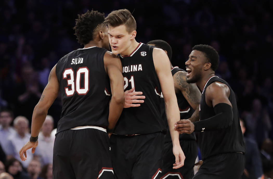 South Carolina forward Maik Kotsar (21) is congratulated by forward Chris Silva (30) after scoring against Florida during the second half of the East Regional championship game of the NCAA men's c ...