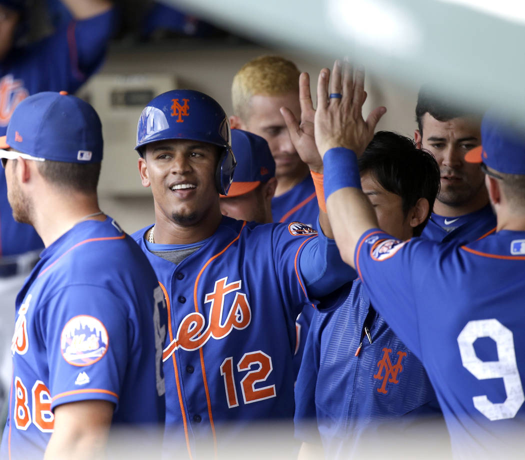 New York Mets' Juan Lagares high fives teammates in the dugout after scoring a run Atlanta Braves in a spring training baseball game, Saturday, March 25, 2017, in Kissimmee, Fla. (AP Photo/John Raoux)