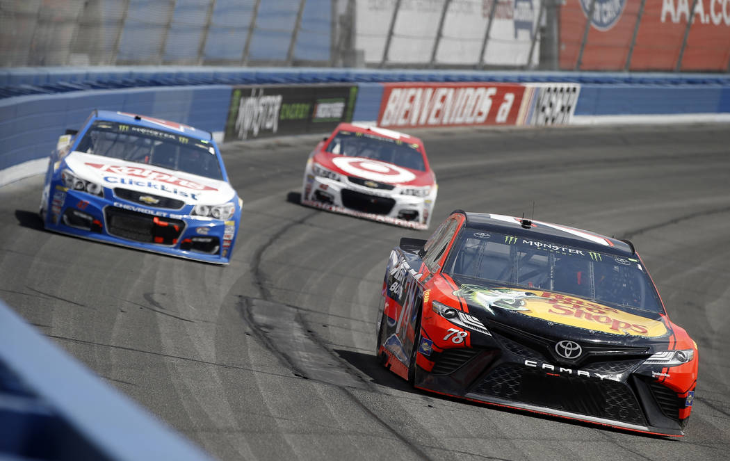 Martin Truex Jr., right, takes the lead, in front of AJ Allmendinger, left, and Kyle Larson, center, in the NASCAR Cup Series auto race at Auto Club Speedway in Fontana, Calif., Sunday, March 26,  ...