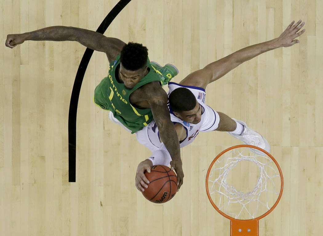 Oregon's Jordan Bell (1) blocks a shot by Kansas' Landen Lucas during the second half of the Midwest Regional final in the NCAA men's college basketball tournament, Saturday, March 25, 2017, in Ka ...