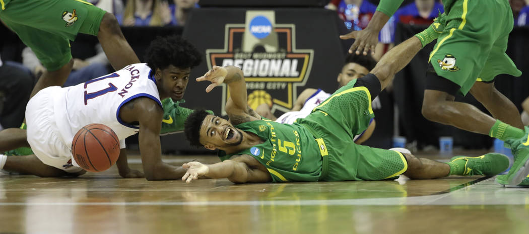 Oregon guard Tyler Dorsey, right, fights for a loose ball with Kansas guard Josh Jackson, left, during the second half of a regional final of the NCAA men's college basketball tournament, Saturday ...