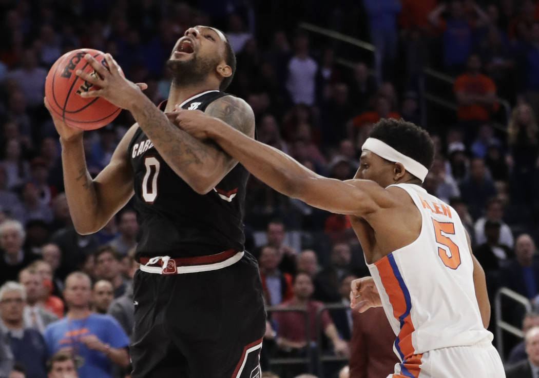 South Carolina guard Sindarius Thornwell (0) is fouled by Florida guard KeVaughn Allen (5) during the second half of the East Regional championship game of the NCAA men's college basketball tourna ...