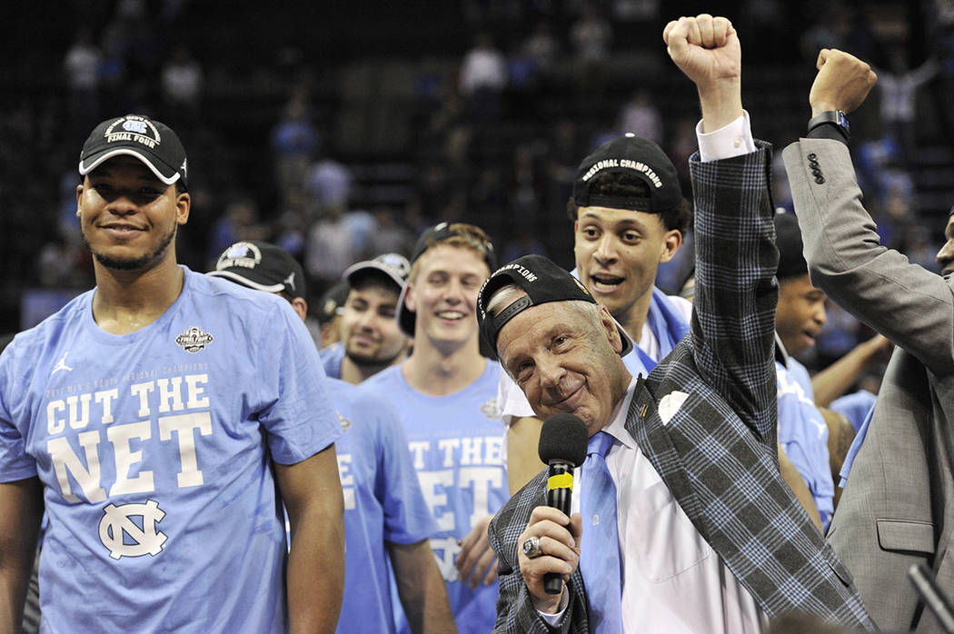 North Carolina head coach Roy Williams, right, celebrates with his team after beating Kentucky 75-73 in the South Regional final game in the NCAA college basketball tournament Sunday, March 26, 20 ...
