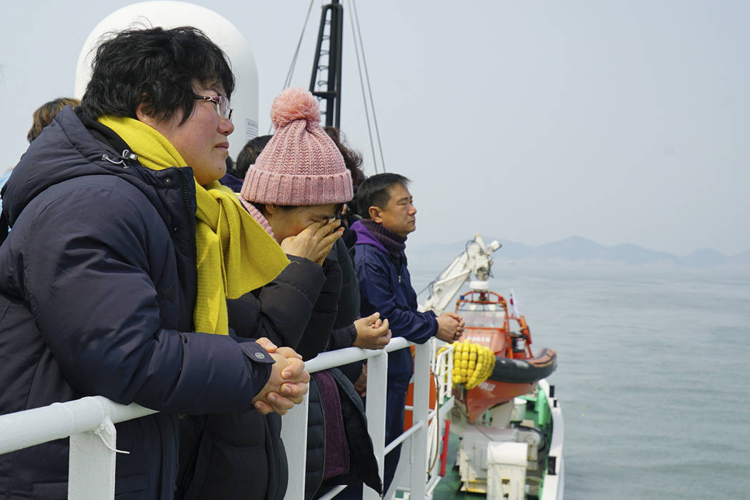 Relatives of the missing victims wipe tears as they attend religious services in waters off Jindo, South Korea, Tuesday, March 28, 2017. South Korean salvage crews on Tuesday found what is presume ...