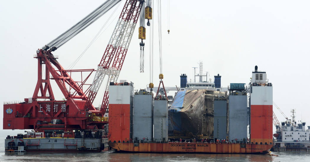 The sunken ferry Sewol is seen on the semi-submersible transport vessel during the salvage operation in waters off Jindo, South Korea, Tuesday, March 28, 2017. South Korean salvage crews on Tuesda ...