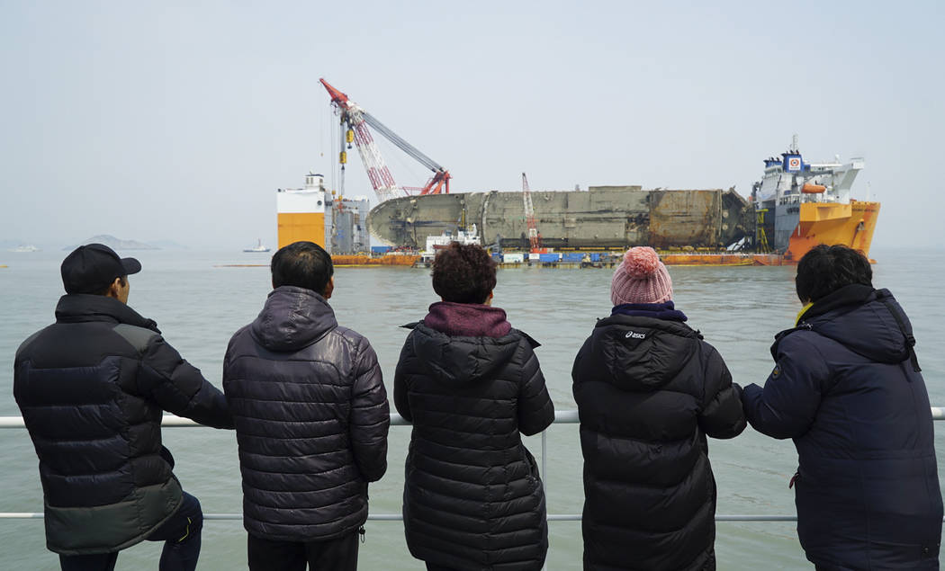 Relatives of the missing victims watch the sunken ferry Sewol sitting on a semi-submersible transport vessel while they attending religious services on a boat, in waters off Jindo, South Korea, Tu ...